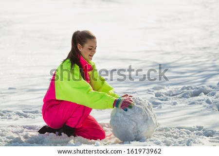 Smiling girl rolling a huge snowball in wintertime