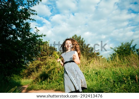 Smiling girl running on the meadow - stock photo