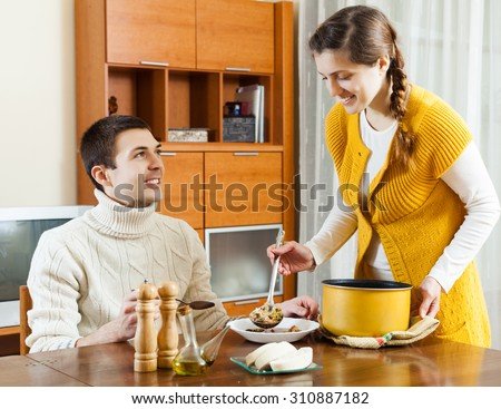 Smiling girl serving soup her beloved man at table - stock photo