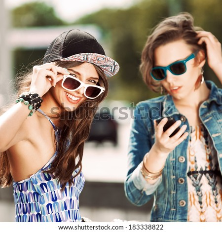 smiling girl set her sunglasses while her friend chats on the phone - stock photo