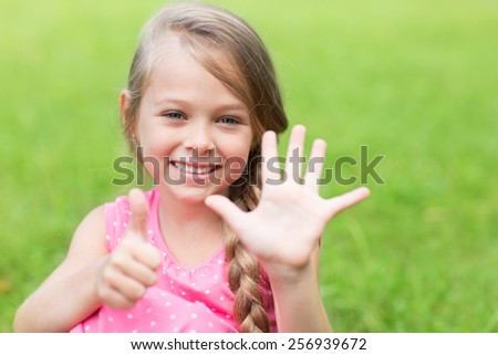 Smiling girl showing thumb up. Girl seven years. - stock photo