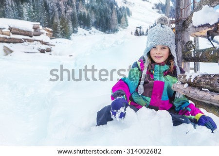 Smiling girl sitting in deep snow near wooden palisade - stock photo