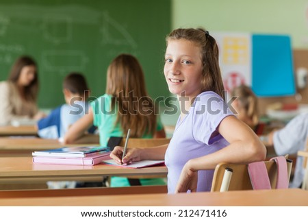 Smiling girl sitting in her classroom. - stock photo