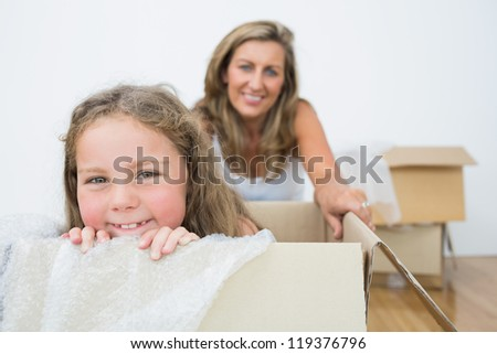 Smiling girl sitting on the box - stock photo