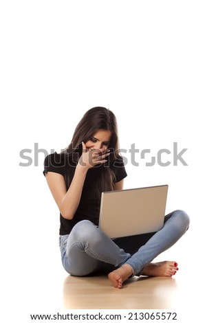 smiling girl sitting on the floor and working on laptop