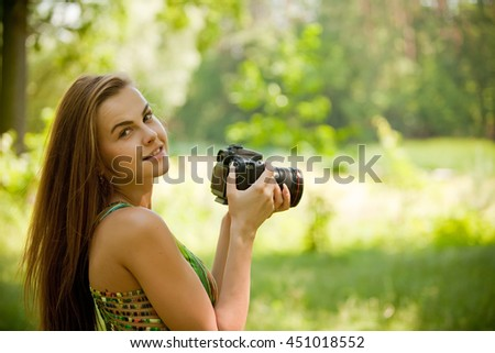 Smiling Girl taking pictures with a camera