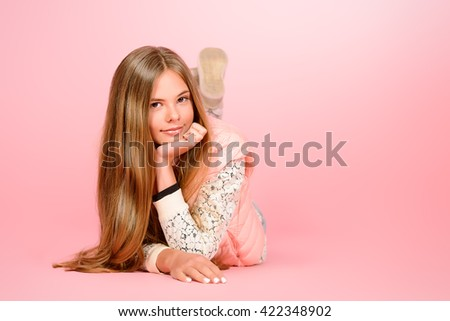 Smiling girl teenager with beautiful healthy long hair lying on a floor over pink background. Studio shot. - stock photo