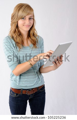 Smiling Girl Using Tablet Computer. Thirteen year old girl smiling at the viewer as she uses a tablet computer. Note: Not Isolated. - stock photo