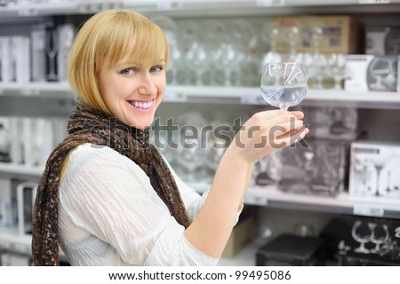Smiling girl wearing scarf holds glass in shop; shallow depth of field - stock photo