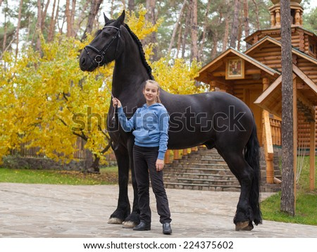 Smiling girl with a black horse - stock photo