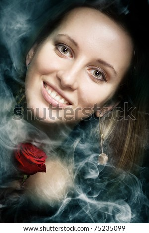 Smiling girl with a red rose in smoke