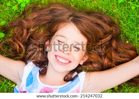 Smiling girl with beautiful brown hair lying on the grass - stock photo