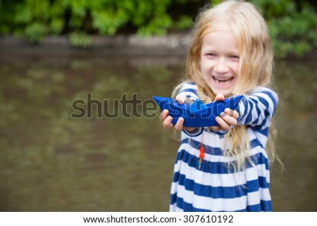 smiling girl with blue paper boat in a puddle after the rain, summer - stock photo