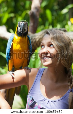 Smiling girl with colorful parrot in the jungle - stock photo