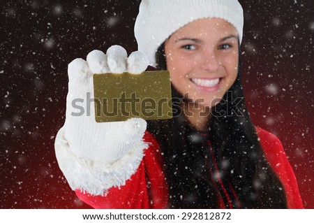 Smiling Girl with Credit Card isolated on a light to dark red background with snow flakes effect. Shallow depth of field with focus on the Credit Card. Christmas Shopping Concept.