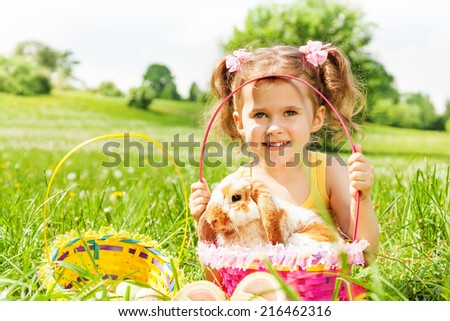 Smiling girl with cute rabbit and baskets in the park during summer time - stock photo