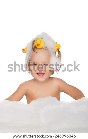 Smiling girl with ducks and soap foam isolated on white - stock photo