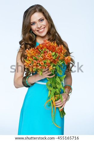 Smiling girl with flowers standing against white background. Isolated. Blue dress.
