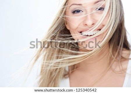 Smiling girl with flying hair on a white background