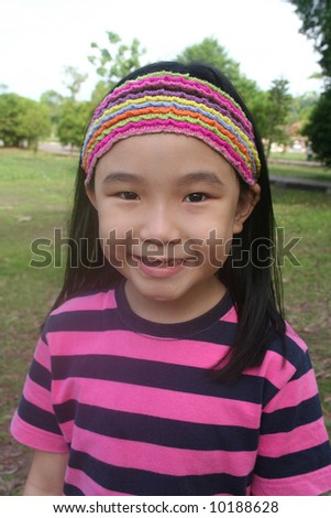 Smiling girl with hair-band without front-teeth in the park - stock photo