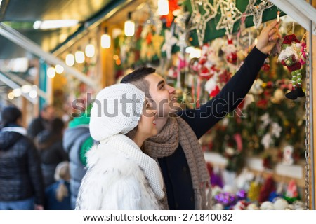 Smiling girl with happy boyfriend choosing Christmas decoration at fair. Focus on woman - stock photo