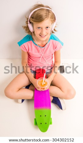 Smiling girl with headphones, glass of juice and skateboard looking up while sitting on a floor at studio against white background. - stock photo
