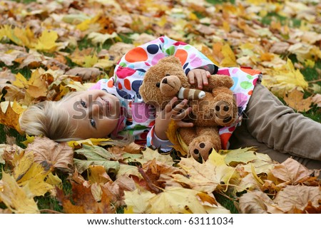 Smiling girl  with her teddy bear in autumn park - stock photo