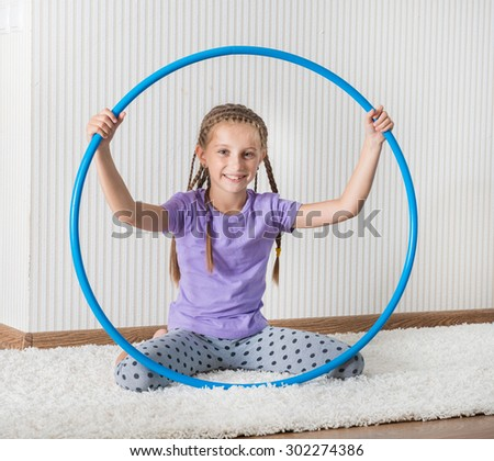smiling girl with hula hoop at home - stock photo