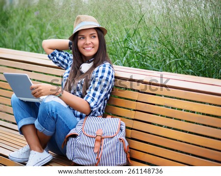 Smiling girl with laptop on the bench - stock photo