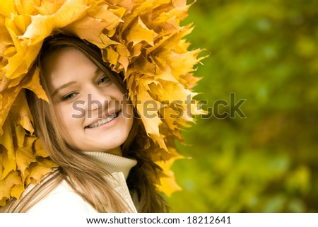 Smiling girl with maple wreath looking at camera on green background