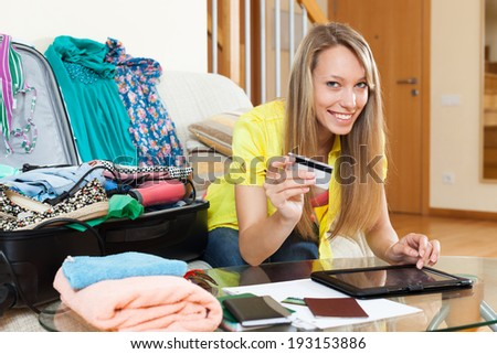 Smiling girl with packed suitcase booking hotel for vacation online - stock photo