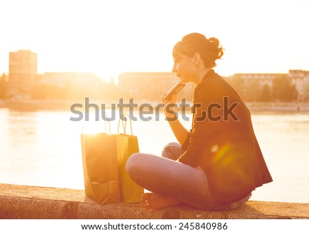 Smiling girl with shopping bags. Girl talking on mobile phone. - stock photo