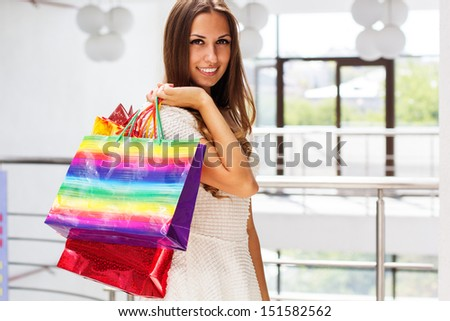 Smiling girl with shopping bags in shop - stock photo