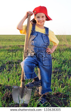 Smiling girl with shovel standing on the field