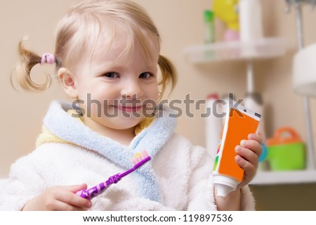 Smiling girl with toothbrush and tube in bathroom - stock photo
