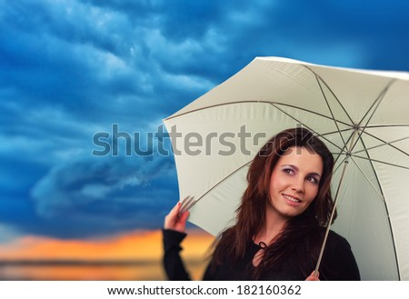 Smiling girl with white umbrella in a rainy day with dark bluish clouds at sunset
