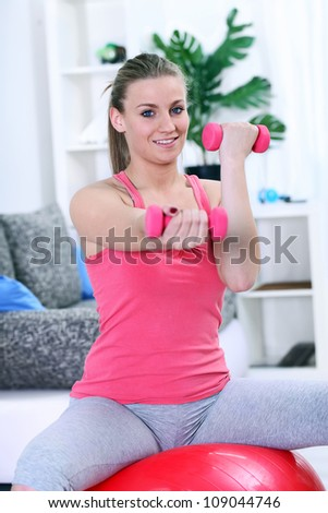 Smiling girl working with fitness ball and dumbbell