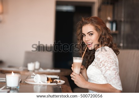Smiling girl 20-24 year old drinking coffee and eating cake in cafe. Looking