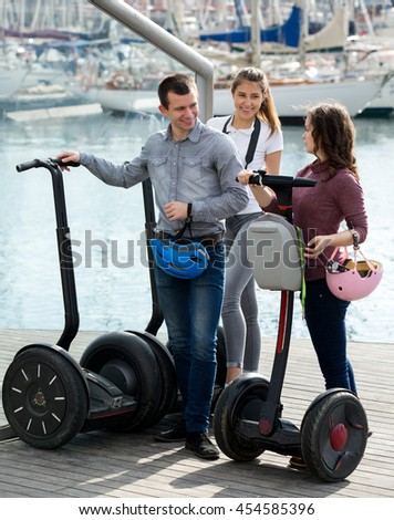Smiling girls and man traveling through city by segways