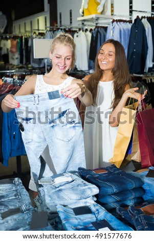 Smiling girls choosing denim trousers together in clothes store