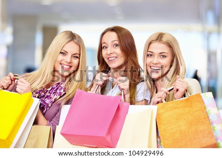 Smiling girls with shopping bags in shop - stock photo