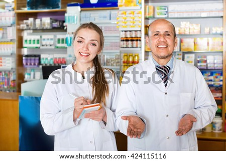 Smiling  glad pharmacist and pharmacy technician posing in drugstore