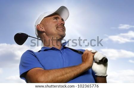 Smiling golfer holding golf club over shoulder - stock photo