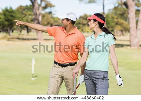 Smiling golfer man pointing while standing by woman on field