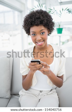 Smiling gorgeous brunette using her smartphone sitting on cosy sofa - stock photo