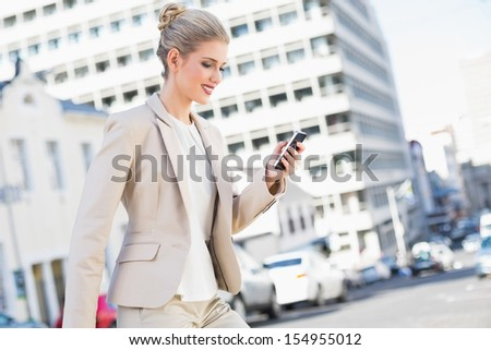 Smiling gorgeous businesswoman text messaging outdoors on urban background - stock photo