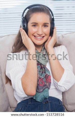 Smiling gorgeous model on cosy sofa listening to music