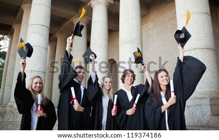 Smiling graduates holding up their hats in front of the university - stock photo