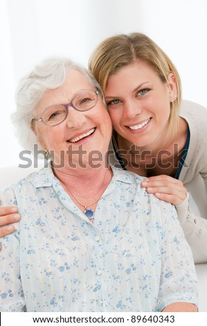 Smiling granddaugther embrace her grandmother at home - stock photo