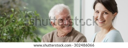 Smiling grandfather and caring granddaughter - panorama - stock photo